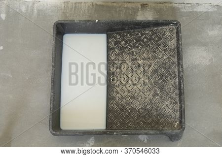 Black Paint Tray With White Primer On Concrete Floor During Interior Construction Project