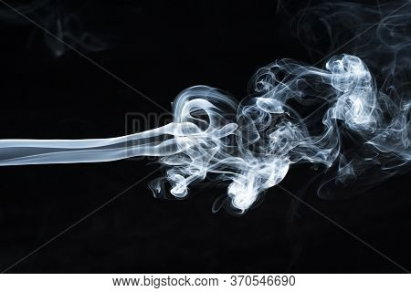 Background Image Of A Wisp Of Smoke On A Dark Background. The Texture Of The Flowing Smoke. Frozen S