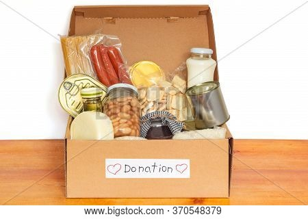 Set Of Grocery Food For Needy In Crisis, Pasta, Beans, Canned Food, And Others In Cardboard Box With