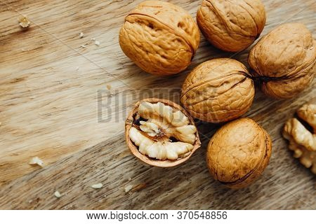 Unpeeled Walnuts On Wooden Surface, Closeup. View From Above. Food Photo. Selective Focus.
