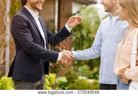 Unrecognizable Real Estate Agent Giving House Key And Shaking Hands With New Home Owners Near Their