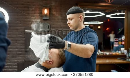 Traditional Ritual Of Shaving. Side View Of Male Barber With A Mustache Covering Face Of Client With