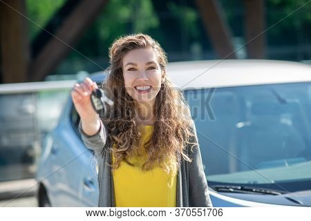 Smiling Woman With Car Key In Outstretched Hand
