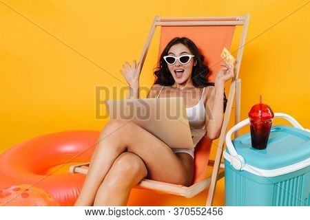 Image of excited woman using laptop and holding credit card while resting in chaise lounge isolated over yellow wall