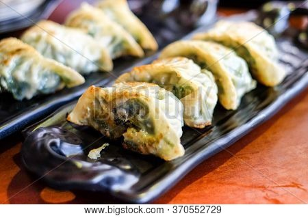 Homemade Gyoza Serve On Black Plate For Chinese Food Background Or Texture.