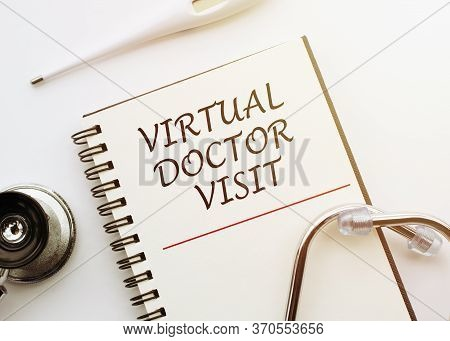 Visit Of A Virtual Doctor - Text On A Laptop On A White Table With A Stethoscope And Thermometer. Vi