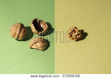 Peeled Nut Along With Its Shells And Another Nut In Shell On Green And Yellow Background
