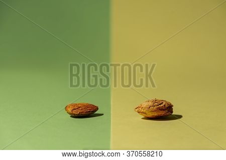 One Raw Almond From The Tree Along With Another One Without Shell On Green And Yellow Background