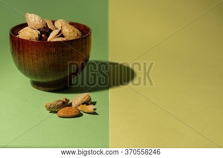 Bowl Of Raw Almonds Next To An Almond Without Its Shell On A Green And Yellow Background