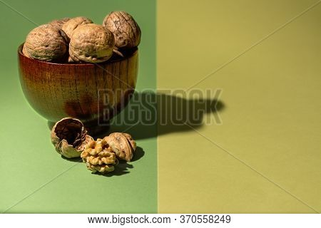 Bowl Of Raw Nuts Next To A Nut Without Its Shell On A Green And Yellow Background