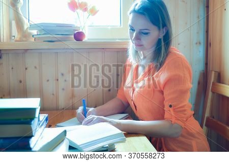 Moscow. Russia. May 2020. Woman Writing A Text On Paper Behind A Desk In The Room. Hobby Writing And