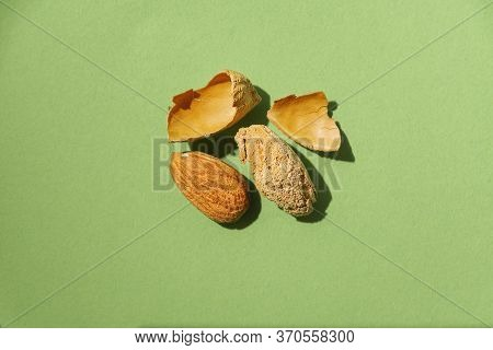 Raw Almond Next To An Almond Without Its Shell On Green Background