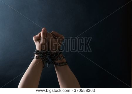 Fists Of Hands Are Chained In Chain On The Black Background, Concept Of Fight And Freedom.