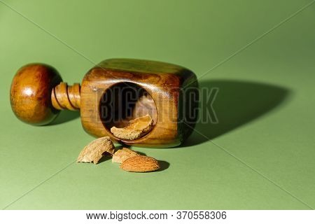 Peeled Almond Next To Its Shells And A Nutcracker, On Green Background