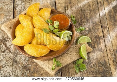 Colombian Empanada With Spicy Sauce. Wood Background