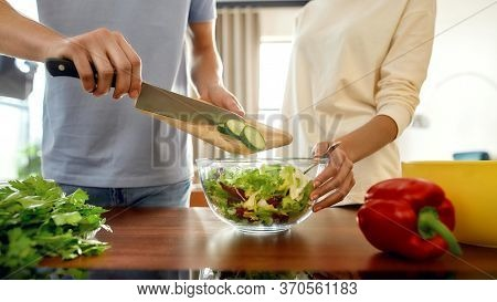 Cropped Shot Of Man Putting Sliced Cucumber In A Dish While Woman Helping Him, Holding The Salad Dis