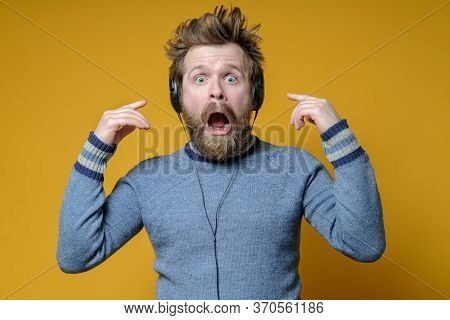 Man In The Headphones Is Ecstatic And Shocked. Shaggy Music Fan In An Sweater Stares In Amazement At