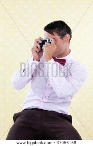 Portrait of retro styled male taking a photo with rangefinder camera