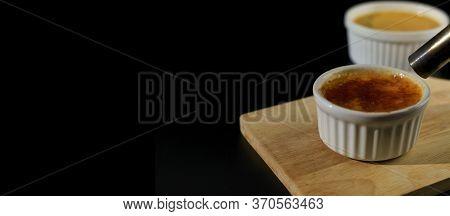 Close Up Homemade Creme Brulee In White Ramekin  With Butane Torch Burn Sugar On Top  On Black Backg