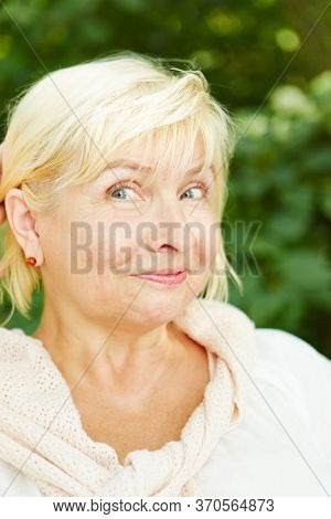 Old blond woman as a senior grins in nature in summer