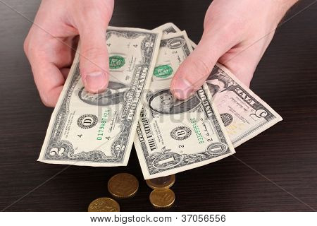 Counting money in hand on wooden table background