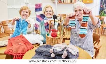 Seniors in the crochet course proudly display self-knitted socks and other clothing