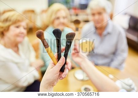 Make-Up Artist shows different make-up brushes in the cosmetics course for seniors