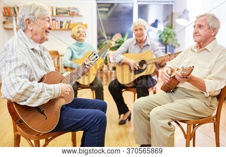 Seniors learn to play guitar together in a guitar course in the retirement home