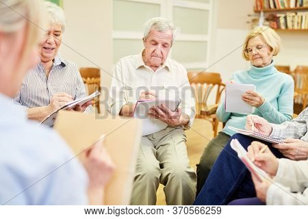 Group of seniors in writing therapy or painting therapy in a retirement home