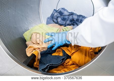 Woman's Hand Putting Colorful Laundry Into An Industrial Washer Of A Dry Cleaner