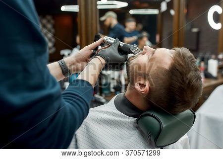 Barbershop Salon. Barber In Black Gloves Making Moustache Correction With Electrical Raser. Focus On