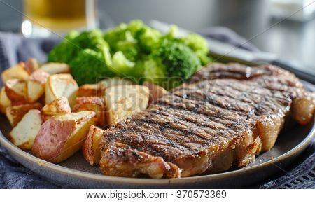 grilled new york steak with broccoli and roasted potatoes
