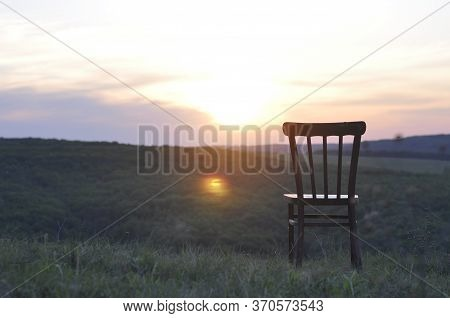 An Old Antique Chair Stands On The Grass. At Sunset. Summer. The Concept Of Meditation And Lonelines