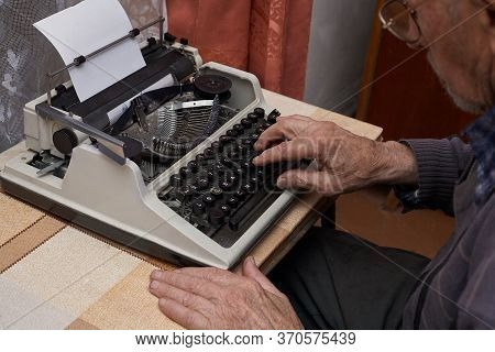 Grandfather Writes On A Typewriter. The Typewriter Is Old. Senior Citizen Works. Horizontal Frame.