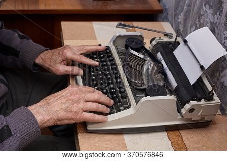 A Senior Citizen Writes On A Typewriter. The Typewriter Is Old. Horizontal Frame.