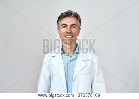 Happy Senior Caucasian Doctor In Medical Uniform Looking At Camera And Smiling While Standing Agains