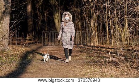 Young Woman In Warm Jacket, Wearing Virus Face Mouth Mask, Walks Her Dog On Country Park Road. Masks