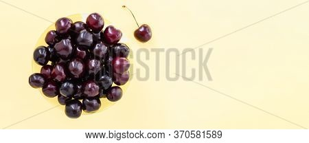 Red Sweet Cherry In A Yellow Cup And One Berry On A Beige Background. View From Above. Banner Cerasu