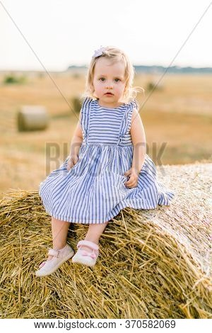 Close Up Portrait Of Cute Pretty Little Baby Girl In Striped Dress Sitting On Hay Stack Or Bale On Y