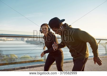 Enjoying Run. Side View Of Happy Young African Couple, Man And Woman In Headphones Laughing While Ru