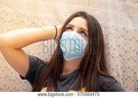 Attractive Brunette Wearing A Surgical Face Mask Looking Up Into The Sky. Optimistic Mood Enjoying T