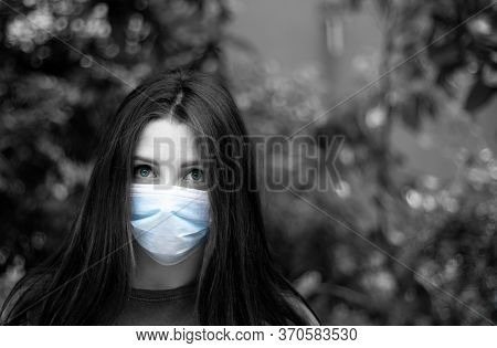Attractive Brunette With A Worried Look Wearing A Surgical Mask. Black And White Image With Only Tea