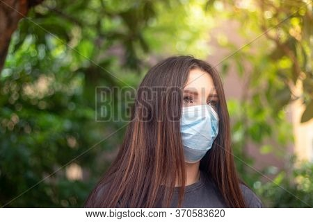 Attractive Brunette Wearing A Light Blue Surgical Mask Looking Into The Distance With A Worried Unsu