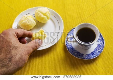 Picking Up The Brazilian Cheese Bread And Coffee Cup And On The Yellow Placemat.