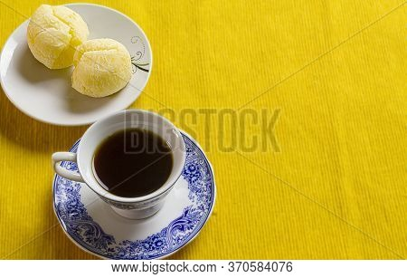 Coffee Cup And Brazilian Cheese Bread On The Yellow Placemat.