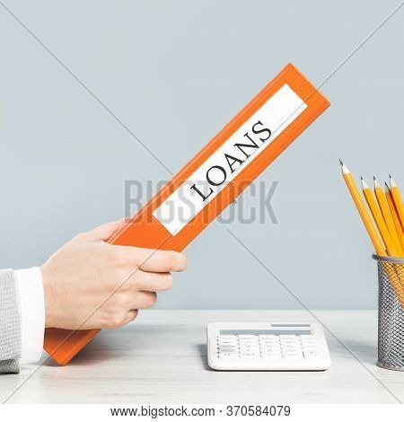 Loans Binder. Finance Concept. Close Up Of Hand Holding Binder In Business Office Space. Bookkeeper
