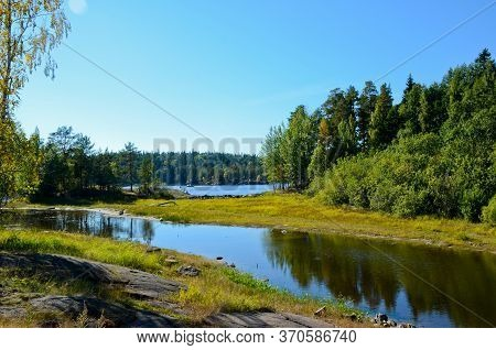 Forest Landscape Of A Lake And Backwater With Calm Water On A Clear, Sunny Day. Green Forest And Roc