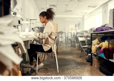 Young Woman Seamstress Sitting And Sewing. Dressmaker Working On The Sewing Machine. Tailor Making A
