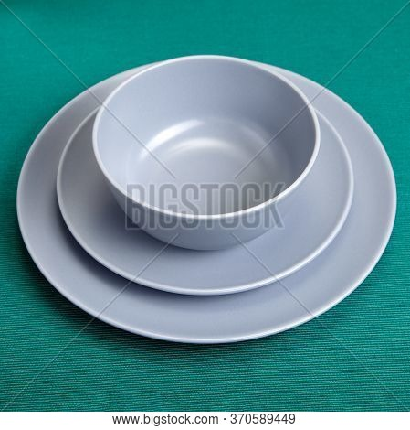A Set Of Kitchen Utensils, Two Plates Of Different Sizes And A Bowl. Ceramic Dishes With Gray Glaze.
