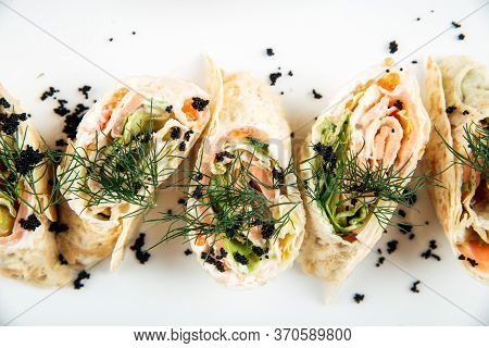 Top View Closeup On Gourmet Slapjack Rolls With Salmon Filling Black Caviar Dill Garnish On A White